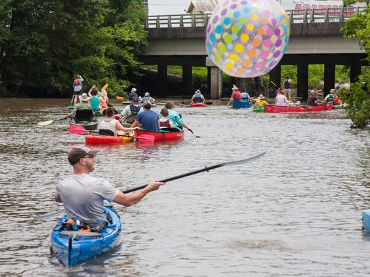 A boat parader bats a beach ball down the Vermilion during last year's festivities.