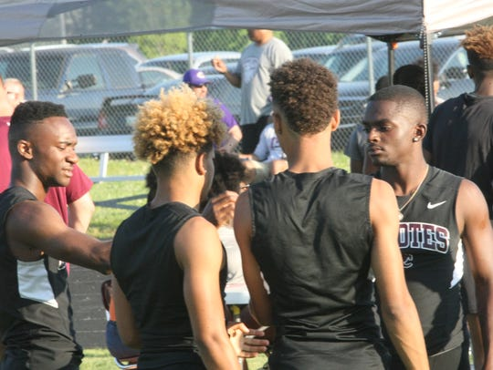 West Creek's track team huddle in the infield during