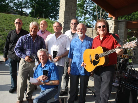 Members of Northern Kentucky Music Legends Hall of Fame, from left, Mike Hodges, Dave Otto, Panny Sarakatsannis, Gary Burbank (kneeling), Mickey Foellger, Mike Reilly of Pure Prairie League, Dennis Hensley of Jordan Recording Studio and Bobby Mackey gather after induction ceremonies at Fort Thomas Tower Park June 5, 2014.