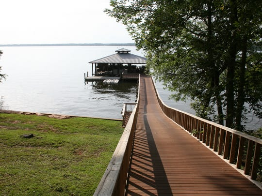 A pier connects the rear of the property to the boathouse at 435 Beau Bois.
