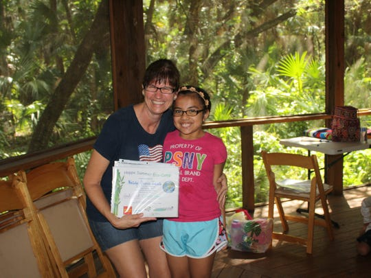 Christy Moore, a math teacher at Three Oaks Middle School, stands with one of the children enrolled in this year's Happe Summer Eco-Camp after the camp's graduation ceremony on Friday, June 16.