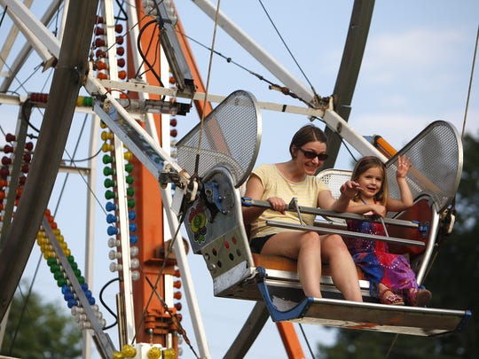 Fair-goers wave to their family from the Ferris wheel at a previous Christian County Fair.
