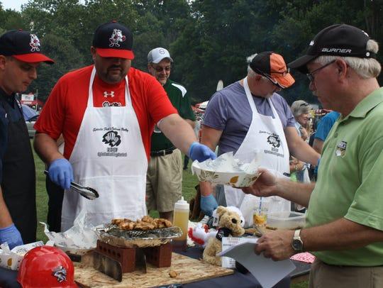 Johnson City Mayor Greg Deemie samples spiedies cooking