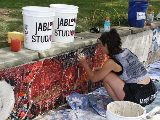 Emily Jablon installs a mosaic at Columbus Park in Binghamton on Monday.