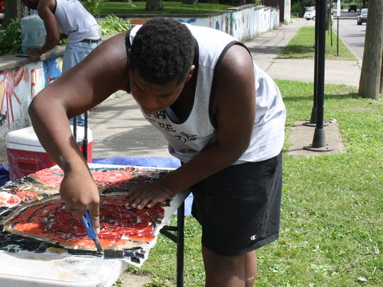 Javon Phillip, 15, of Binghamton, prepares a mosaic to be installed at Columbus Park in Binghamton.