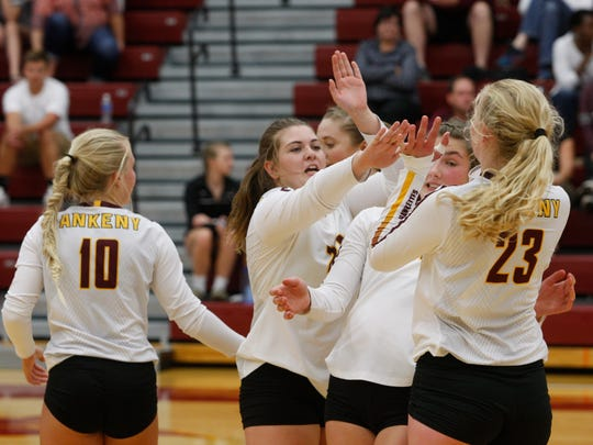 Ankeny's Allycia Parrish, left, tries to high-five Phyona Schrader while teammate Isabelle Vacek gets out of the way during a match against visiting Dowling Catholic on Sept. 5. The 13th-ranked Hawkettes built a 2-0 lead before No. 5 Dowling rallied for a 3-2 victory.