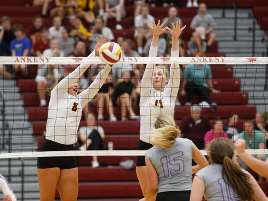 Ankeny's Riley Kenworthy, left, and Sara McCullough try for a block during the Hawkettes' win over Johnston on Aug. 22, 2017.