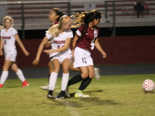 West Creek's Emily Rivera (13) taps the ball away from
