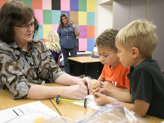 Science and math teacher Sheri Pierce works with Jace Cook, 7, (center) and Carson Thacker, 6,  to make cars during the STEM club at Houston Elementary in Gilbert on Monday, October 2, 2017.