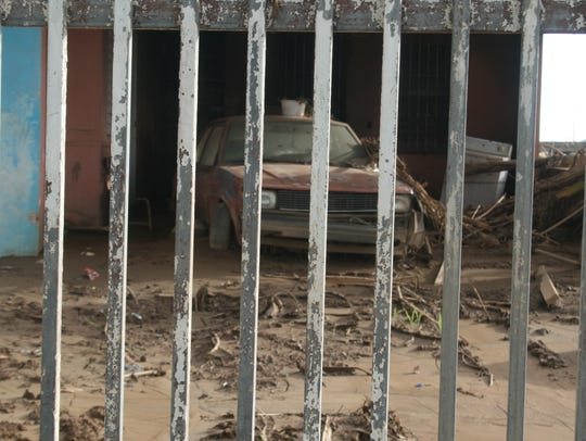 A car in Anasco is still covered in mud in a driveway