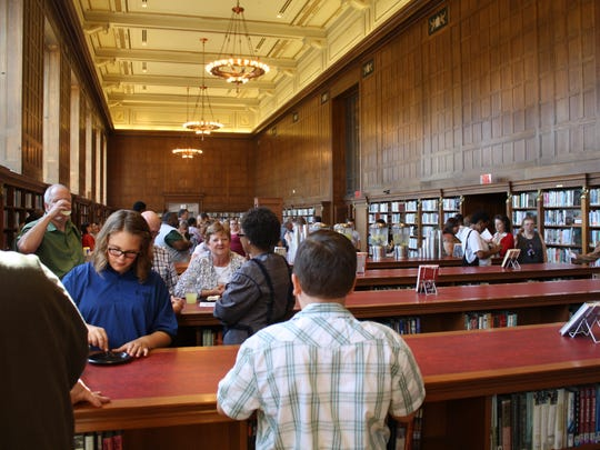 Visitors celebrate the library's centennial withj a birthday cake and children's time capsule activities.
