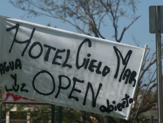 A crude sign advertises that a local hotel is back