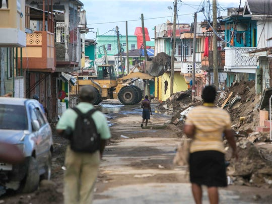 An excavator scoops up piles of debris from the streets of Roseau, the capital of Dominica, as they continue to clean up and rebuild from the destruction caused by Hurricane Maria.