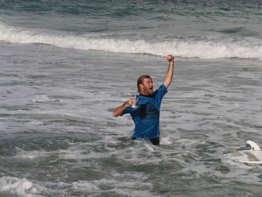 Surfer Aaron Cormican celebrates in final heat with a beer Nov. 5 at the King of the Peak surf contest.