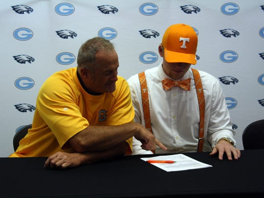 Bass Cooper, right, and Gibbs coach Geff Davis look at Cooper's letter of intent to play baseball at Tennessee.