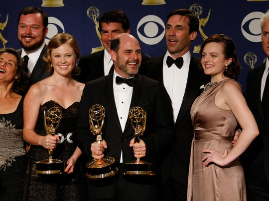 The cast and crew of 'Mad Men' pose at the 61st annual Primetime Emmy Awards. In the center holding trophies are Kater Gordon and Matthew Weiner.
