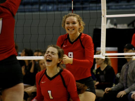Laingsburg's Grace Gregg and Maya Ferland celebrate a winning point late in the Class C semifinal, Nov. 17 at Battle Creek's Kellogg Arena.