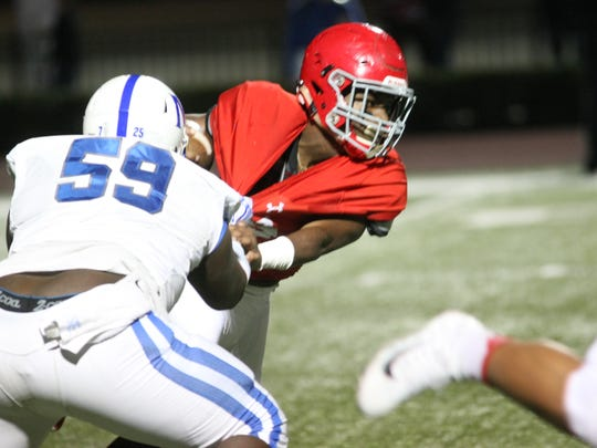 Brentwood Academy's Mario Pleasant tries to escape the tackle of McCallie's Richmond Coney (59) during the first half of their Division II, Class AAA state semifinal game Friday night.
