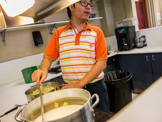 Estero High School culinary junior Dat Nguyen stirs