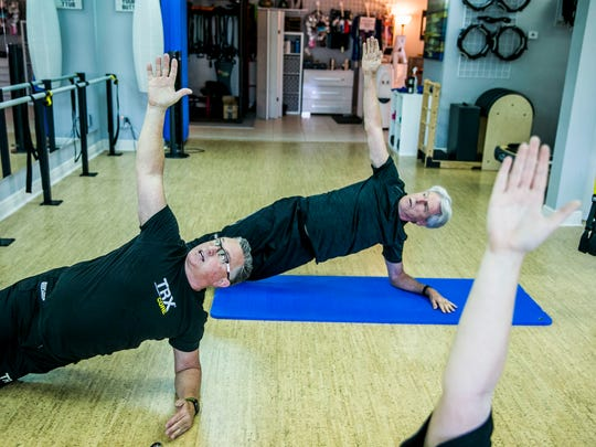 Michael Elliott, left, leads a high-intensity training class as Jim King, right, follows along at Core to Core Fitness in Naples on Thursday, Jan. 18, 2018.