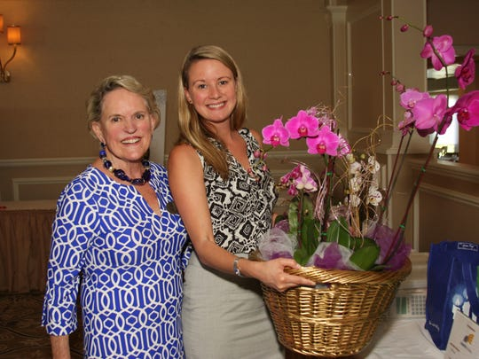 Samantha Ramlall, Children's Home Society Charitable Giving manager, helps Nancy Briggs, bridge committee member, to her car with her beautiful prize of Adamson's Orchids. There were over 25 chance drawings at the bridge tournament.