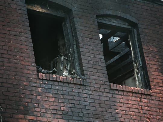 Charred bricks are visible on the back of the Canby Park rowhome, the site of a Sept. 24, 2016 fire that claimed the lives of three firefighters.