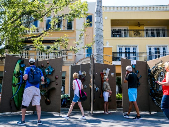 Attendees walk along 5th Avenue in downtown Naples