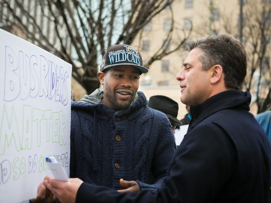 "Chris Buccini talks with protestor D. Marque Hall asking him about the sign he was holding up. ""The Coalition to Keep Bus Service on Rodney Square"" rallied Monday morning at Rodney square then marched several blocks to where they were dedicating a new parking structure at Orange and 9th Street."