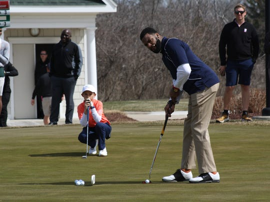 Former Michigan football standout Braylon Edwards uses a side stance putting stroke to win the putting challenge and the overall scoring.