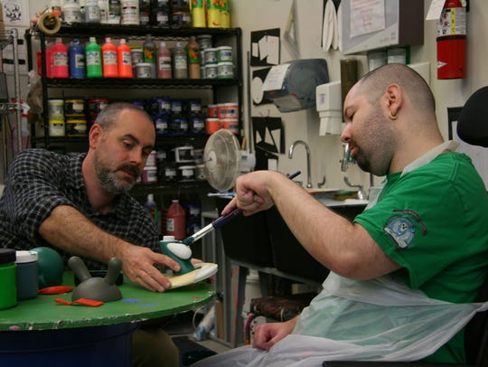Joe Matousek  assists artist Mike Arin on his latest Munny Doll sculpture.