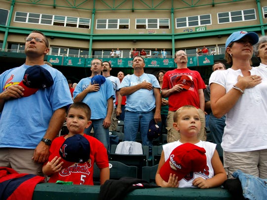 Mark Beem, of Preston, Missouri, from left, shows his respect for the United States by standing for the Star Spangled Banner with his family, Daxton Beem, 6, Lawson Beem, 5, and his wife, Staci Beem, moments before the start of the Northwest Arkansas Naturals versus Springfield Cardianals baseball game at Hammons Field in Springfield, Missouri, Thursday, July 10, 2008.