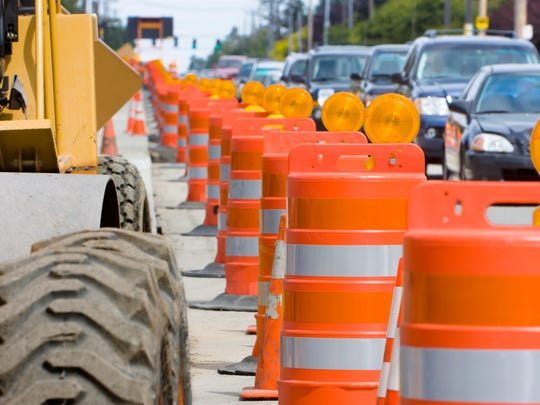 A row of bright Orange construction barriers separate construction from traffic.