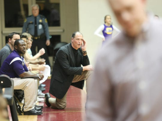 Clarksville HIgh coach Ted Young (kneeling) shouts instructions to his team during a boys basketball game.