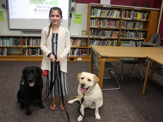 Fifth grader Hailey Smallacomb, 10, works with Palmer Elementary School's two therapy dogs Riley (left) and Gracie (right).