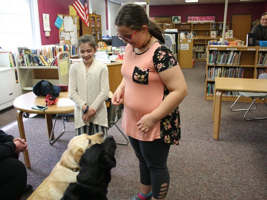 Fifth graders Hailey Smallacomb, 10, and Anne Coleman, 10, work with Palmer Elementary School's two therapy dogs.