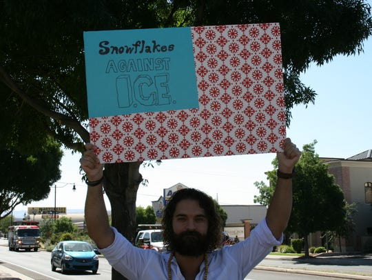 "Logan Kendell holds a sign  reading ""Snowflakes against"