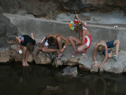 Bailey Hintze (from left), Kobe Driggs, Sydney Houser and Haden Hintze focus on finding a crawdad July 11, 2018, at Veyo Pool and Crawdad Canyon.