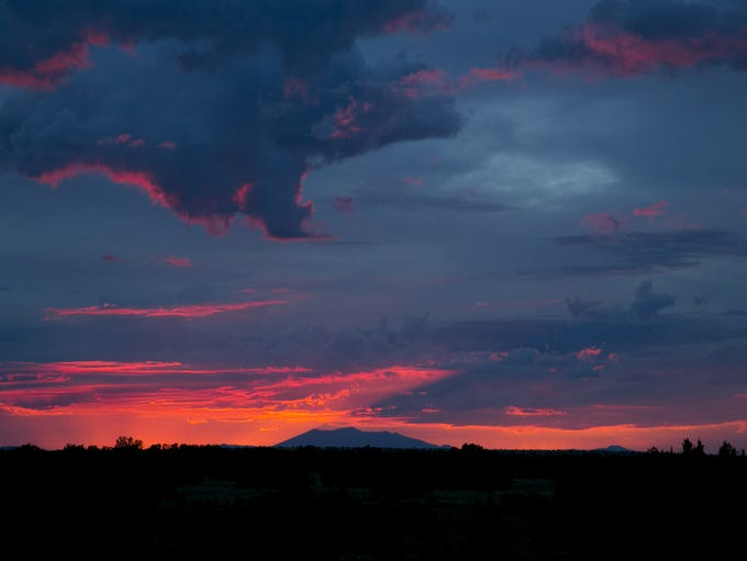The San Francisco Peaks are seen in the distance as