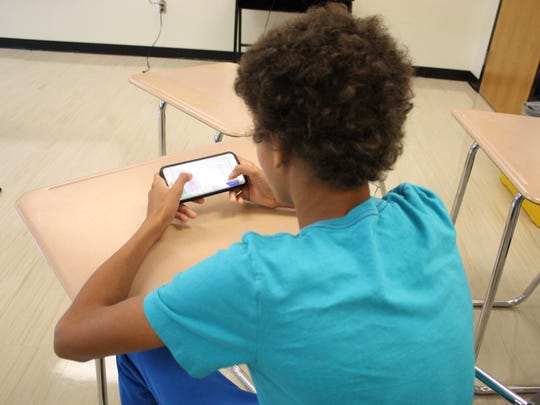 Aden Degroat, 14, of Windsor, plays Fortnite on his phone inside a Windsor High School classroom.