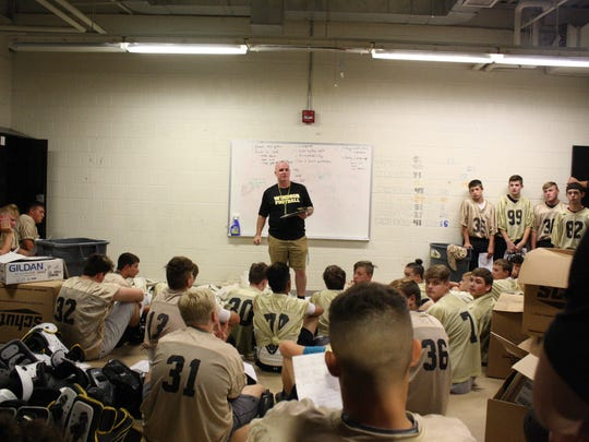 Windsor football coach Tim Hogan speaks to varsity and junior varsity players in the locker room prior to the team's midnight practice.