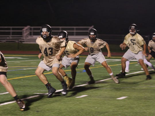 Windsor football players warm up during the first practice of the season. As per tradition, the practice was held at midnight.