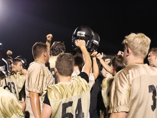Windsor football players bring it in during one of the first huddle of the season.