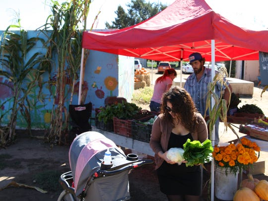 Shoppers examine Stevie Hall's produce from the land