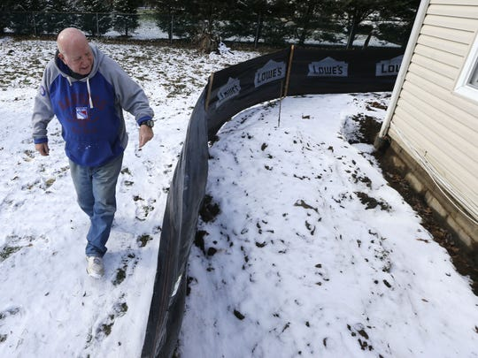 Retired Keyport teacher Dick Woolf observes the trench dug near the foundation of his Middletown home.