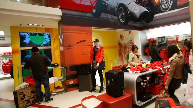 Customers look at clothing at a Ferrari store in Milan, Italy, which already sells branded fashion items.<252><137>— 399-euro ($494) carbon frame Oakley sunglasses, 445-euro ($550) watches and a 1,250-euro ($1,546) LaFerrari lamb nappa leather jacket — not all products bearing the Formula 1 Scuderia logo are of the same high quality.People look at clothing in a Ferrari Store in Milan, Italy, Tuesday, Dec. 9, 2014. Ferrari's sleek sports cars and souped-up Formula 1 racing machines have made the prancing horse logo among the world's most powerful brands, and now the company is preparing for a public company listing and wants to cash in on its brand recognition as a luxury goods company. (AP Photo/Luca Bruno)<252><137>