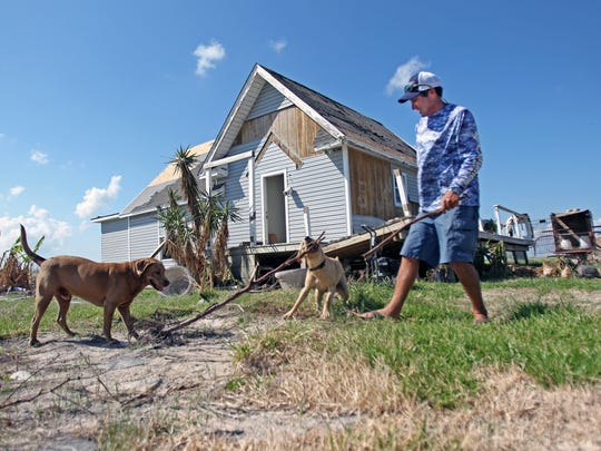 Scott McCune plays with his dogs, Trigger and Kona, among the ruins of his rural homestead ravaged by Harvey.