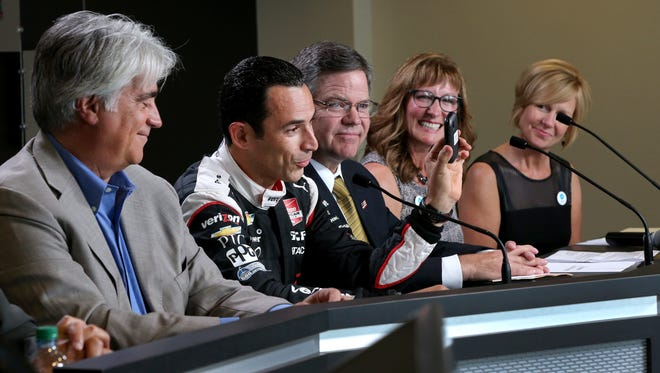 Team Penske's Helio Castroneves talks about the phone he is going to drop off while launching the Indiana Hopeline Drive campaign Thursday, May 7, at the Indianapolis Motor Speedway. IMS CEO Mark Miles,left, Verizon's Neil Krevda, right, of Helio, domestic abuse survivor Dottie Davis and Laura Berry, Indiana Coalition Against Domestic Violence, right.