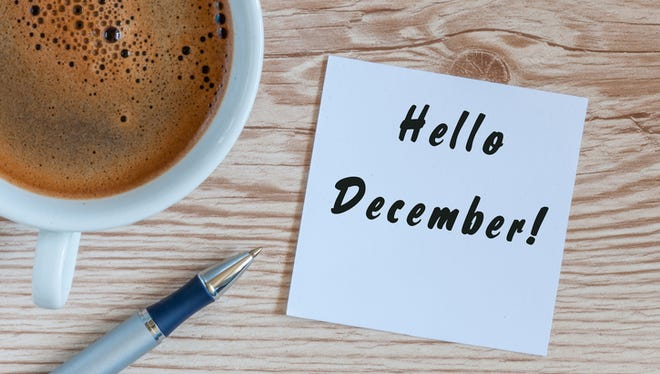Hello December written on paper near morning coffee cup.