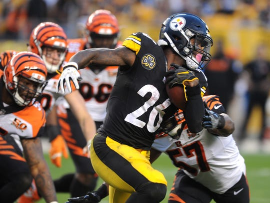 Pittsburgh Steelers running back Le'Veon Bell (26) runs by Cincinnati Bengals defenders including linebacker Vincent Rey (57) in the third quarter at Heinz Field.