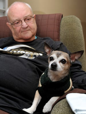 Russell Hackman of Madison sits with his Chihuahua Webster, who he credits with saving his life after alerting him to a gas leak.